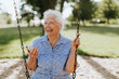 Leinwanddruck Bild - Cheerful senior woman listening to music at a playground