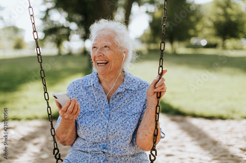 Leinwanddruck Bild Cheerful senior woman listening to music at a playground