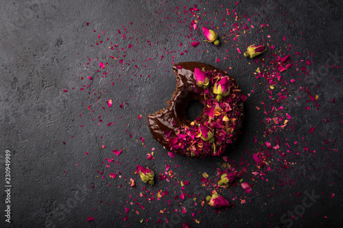 baked chocolate donut with chocolate and dried rose topping, top view, dark background