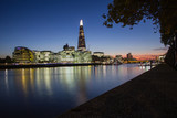 London's south bank showing city hall and shard skyscraper's colourful reflections in the River Thames at dusk