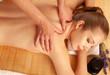 Beautiful young woman having a massage treatment in spa salon - wellness