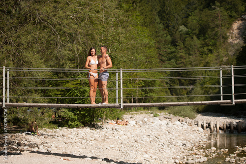 Fridge magnet Active young couple on a bridge over alpine river on hot summer morning