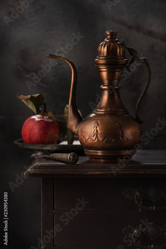 Still life with a copper jug for wine and an apple © Rozmarina