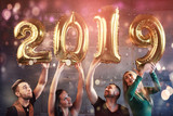 A group of merry young people hold numbers indicating the arrival of a new 2019 year. The party is dedicated to the celebration of the new year. Concepts about youth togetherness lifestyle - 230966120