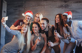 Group beautiful young people doing selfie in the new year party, best friends girls and boys together having fun, posing emotional lifestyle people. Hats santas and champagne glasses in their hands - 230966168