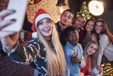 Group of сheerful old friends communicate with each other and make a selfie photo. New Year is coming. Celebrate the new year in a cozy home atmosphere - 230966199