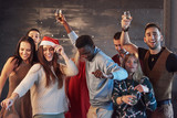 Party with friends. They love Christmas. Group of cheerful young people carrying sparklers and champagne flutes dancing in new year party and looking happy. Concepts about togetherness lifestyle - 230966341