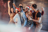 Party with friends. They love Christmas. Group of cheerful young people carrying sparklers and champagne flutes dancing in new year party and looking happy. Concepts about togetherness lifestyle - 230966364
