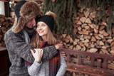 christmas and couple concept - smiling man and woman in hats and scarf hugging over wooden country house and snow background - 230966509