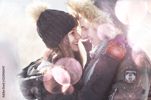 Leinwanddruck Bild christmas happy couple in love embrace in snowy winter cold forest, copy space, new year party celebration, holiday and vacation, travel, love and relations