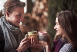 Young couple having breakfast in a romantic cabin outdoors in winter. Winter holiday and vacation. Christmas couple of happy man and woman drink hot wine. Couple in love - 230966790