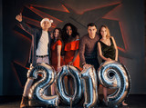 The new 2019 is approaching. A group of merry young multinational people in Santa's hat with silver numbers and throwing confetti at the party. Happy New Year. - 230967188