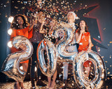 A group of fun young beautiful multinational people throwing confetti at a party. Celebration of 2020. - 230967708