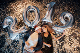 New Year party. A man and a woman celebrate with balloons and lie in confetti - 230967799