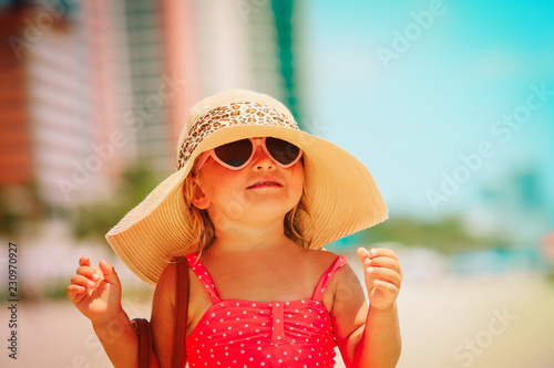 cute little girl with big hat on city beach