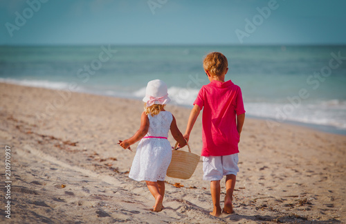 little boy and girl walk on summer beach