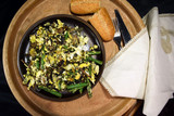 Fried champignons, green beans and eggs on the served table. Ready meal on a wooden dish. Black background. Selective focus. - 230974360