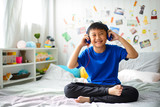 Little asian boy using headphones and smiling happy while listening music - 230976142