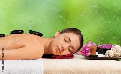 Young woman in spa salon, getting stones