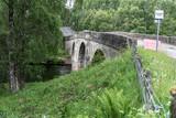 Einsame Straße verläuft über eine malerische Steinbrücke um Fluß zu überqueren umringt von Bäumen in Schottland - 231003333