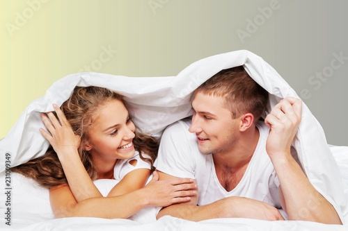 Young beautiful couple in bed at home