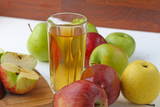 Apple juice in a glass and apples on the table.