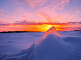 Transparent piece of ice on the snow against the backdrop of a winter sunset