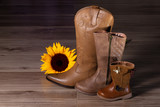 Three brown cowboy boots of different sizes and a sunflower on wooden floor - 231017197