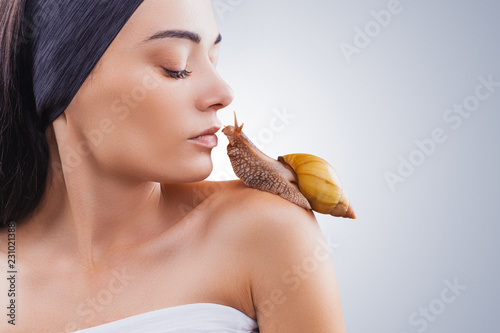 Beautiful brunette young woman with giant Achatina snail on light background - 231021388