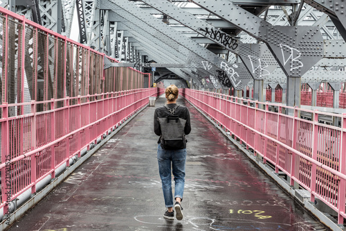 Leinwanddruck Bild Solo casual woman walking the cycling lane on Williamsburg Bridge, Brooklyn, New York City, USA on overcast day.