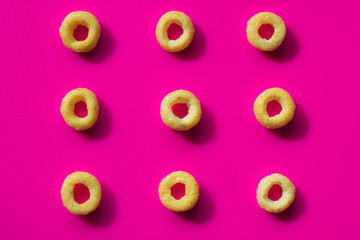 pastel pink background with yellow cereals