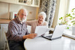 Leinwanddruck Bild - Mature couple sitting at kitchen table with laptop looking through financial papers, having little jam with the pension contributions.