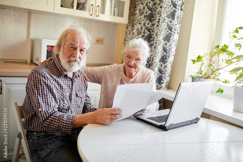 Leinwanddruck Bild Mature couple sitting at kitchen table with laptop looking through financial papers, having little jam with the pension contributions.