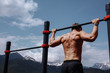 Caucasian male athlete with fit torso and strong hands doing chin ups outdoor. Handsome blonde sportsman pulls up on stadium horizontal bar. Chin up bar exercises.
