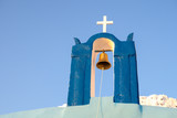 Blue top of a chapel with a white cross and a golden bell. Santorini island, cyclades of Greece.