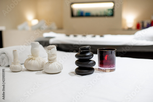 Herbal bags with stones for massage on the white towel indoors - 231055911