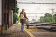Woman with backpack and umbrella is waiting for a train on railroad station. Travelling during rain at autumn season. Travel concept