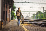 Woman with backpack and umbrella is waiting for a train on railroad station. Travelling during rain at autumn season. Travel concept  - 231072981