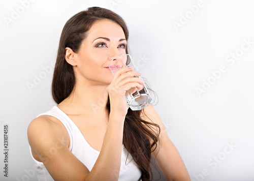 Leinwanddruck Bild Positive happy smiling woman with healthy skin and long curly hair drinking pure water on white background. Closeup portrait