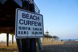 Beach in morning with curfew sign - 231082199