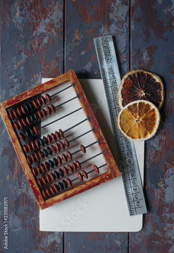 vintage abacus with notebook, pen and dried orange slices on rustic wooden table, hugge concept, top view, selective focus - 231083971