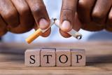 Man Breaking Cigarette Over Wooden Stop Blocks - 231100749