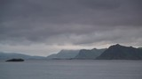 Sea landscape with mountains on horizon, Austvagoya island, Lofoten Norway. Hazy rainy cloudy day, overcast weather in summer. Time lapse - 231101101