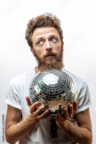 Tired or pensive DJ man holds a disco mirror ball looking aside at blank space isolated over white background with copyspace - 231111110