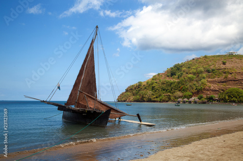 An old sailing ship stands off the coast of Nosy Be Island