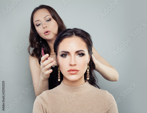 Hairdresser woman with beautiful female model. Fashion beauty portrait