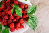Red fresh raspberries on white rustic wood background. Plate with natural ripe organic berries with green leaves.flat lay with copy space