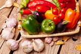 Cherry tomatoes, peppers, garlic, eggplants in a wicker basket. Fresh vegetables on a wooden table..