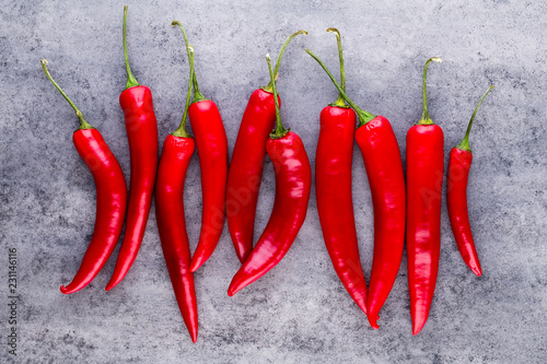 Wall mural Chili cayenne pepper on grey background.