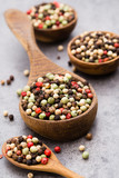 Peppercorn mix in a wooden bowl on grey table. - 231146327